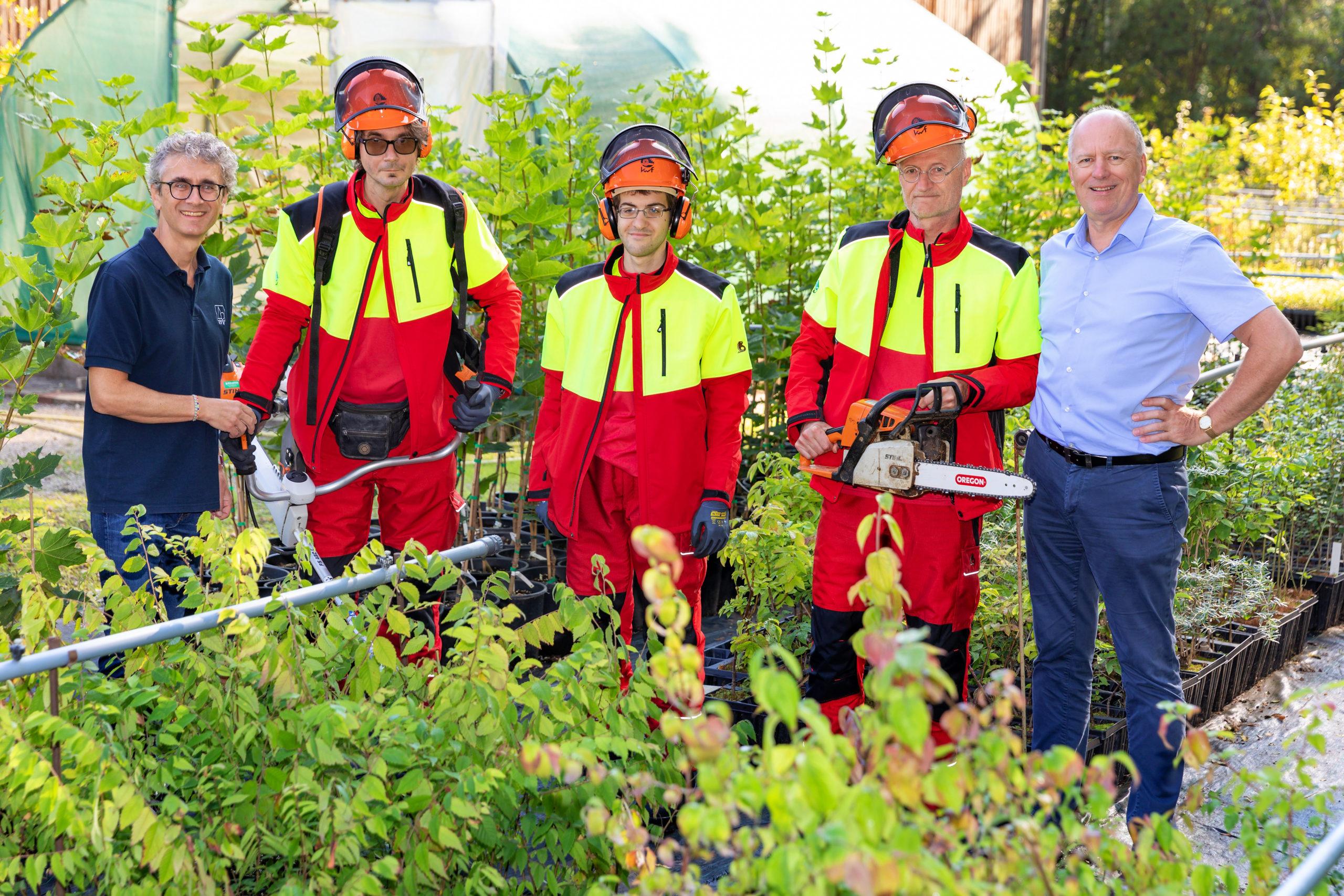 % Personen stehen in einem Forstgarten. Drei Personen tragen eine Sicherheitsausrüstung.