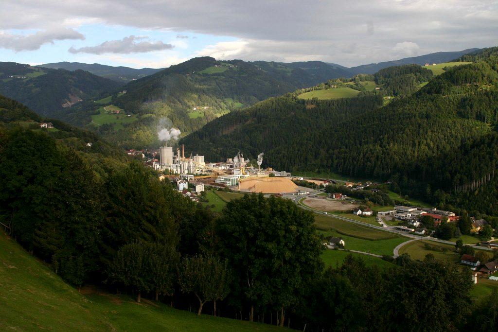 Blick vom Hügel auf Papierfabrik mit rauchendem Schlot