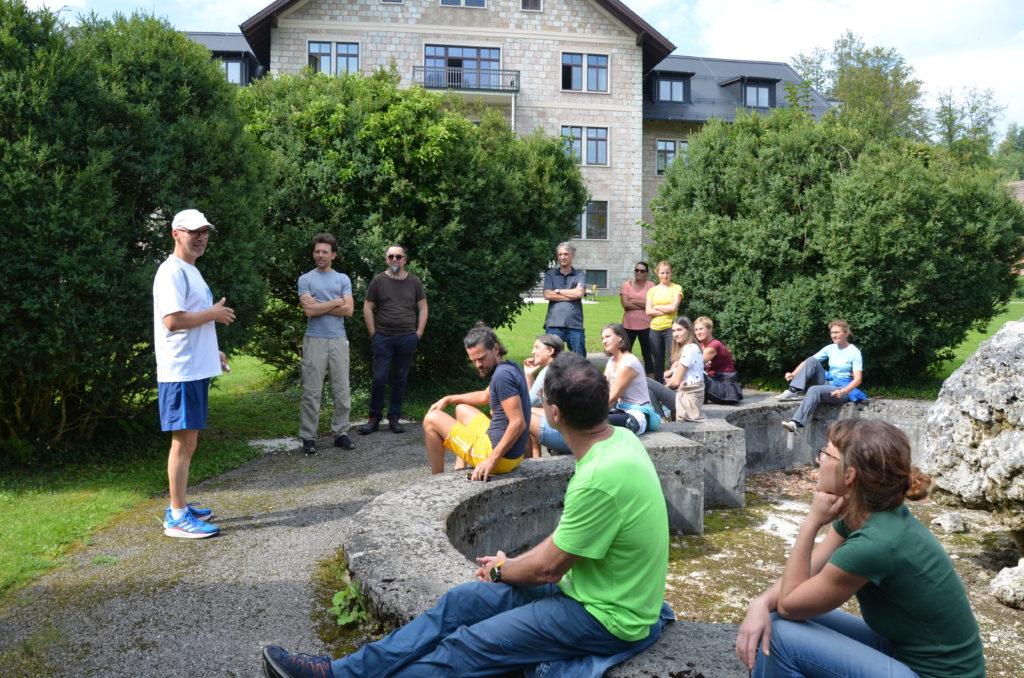 Menschengruppe im Freien lauscht dem Lauftherapeuten